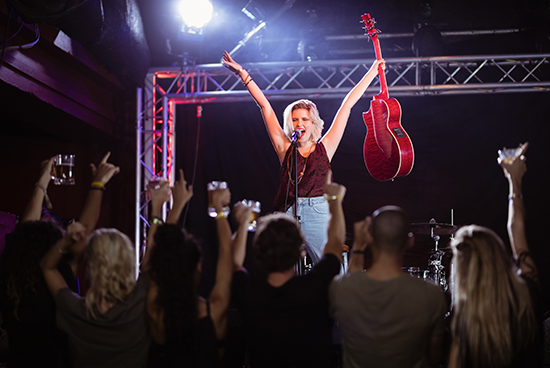 female-performer-with-arms-raised-singing-during-m-PU4GYDW